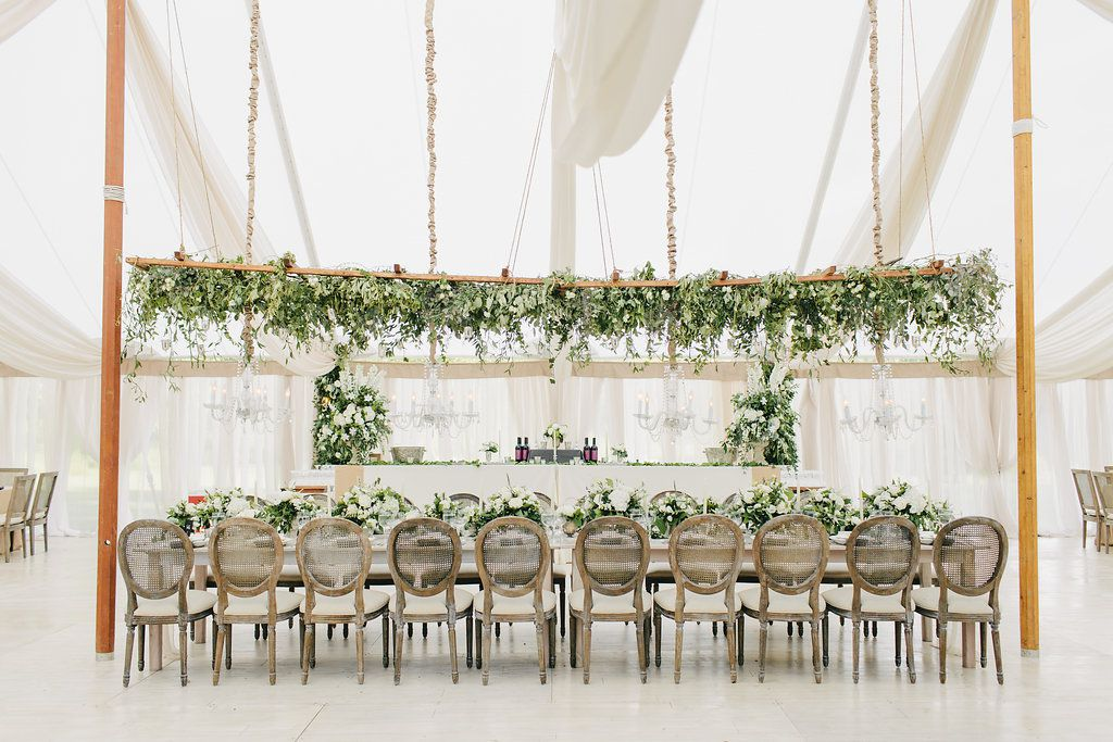 A hanging floral display is perched above a head table.