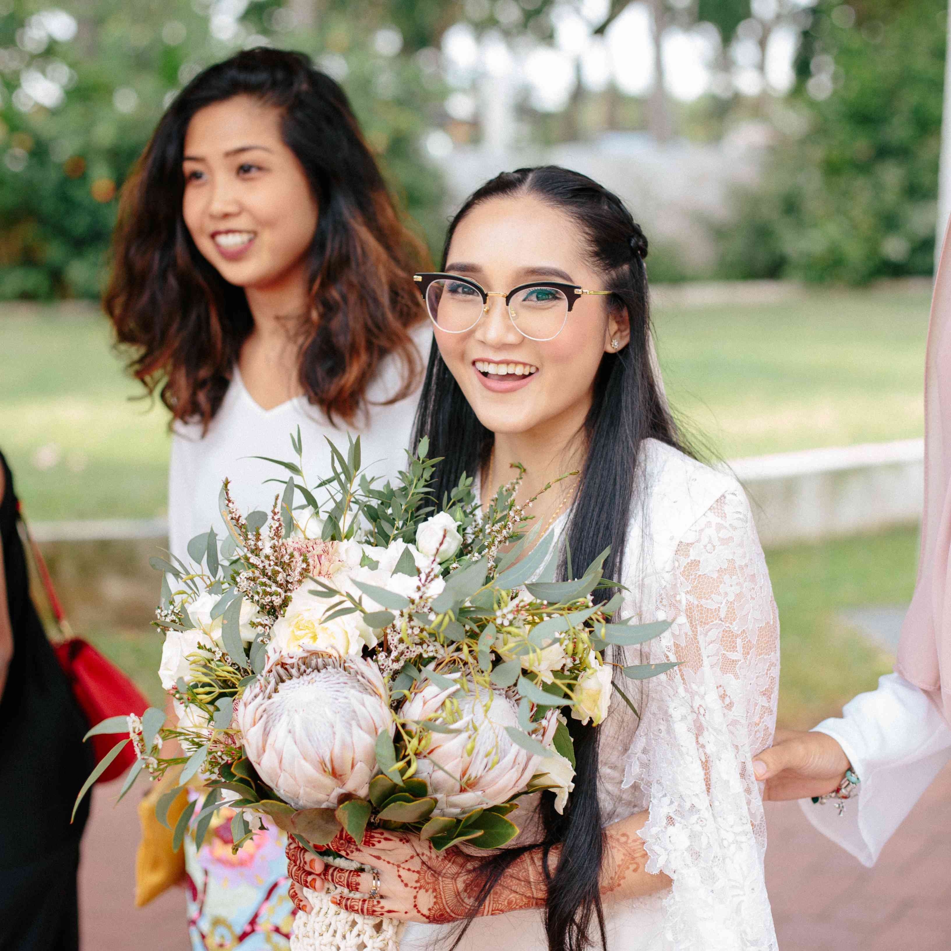 Bride wearing semi-rimmed glasses holding her bouquet and smiling