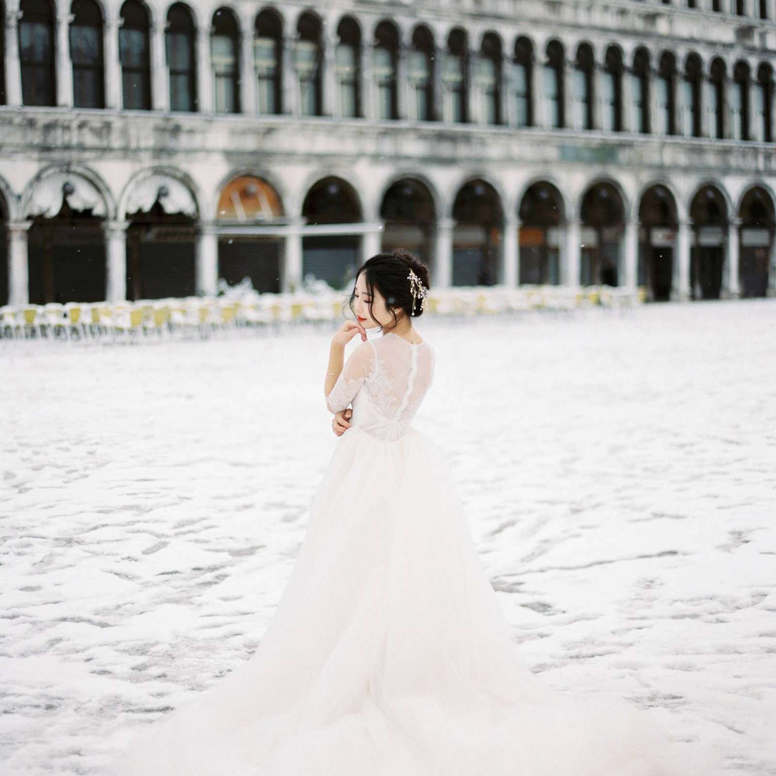 Bride in her wedding gown posing in the snow outside