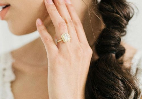 Woman holding her hand to her face wearing a diamond engagement ring
