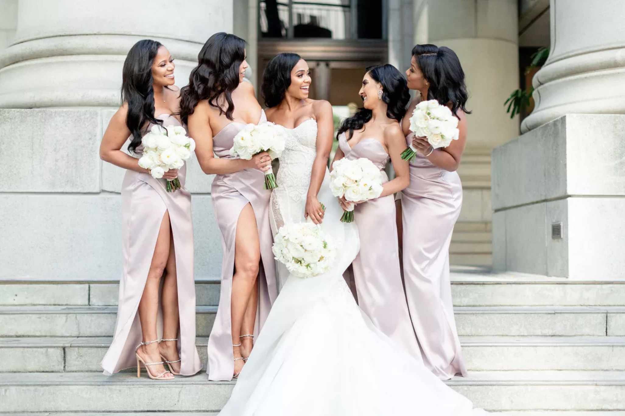 Bride with bridesmaids in matching dresses on steps