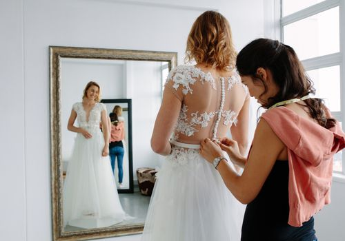 Bride and tailor during dress fitting