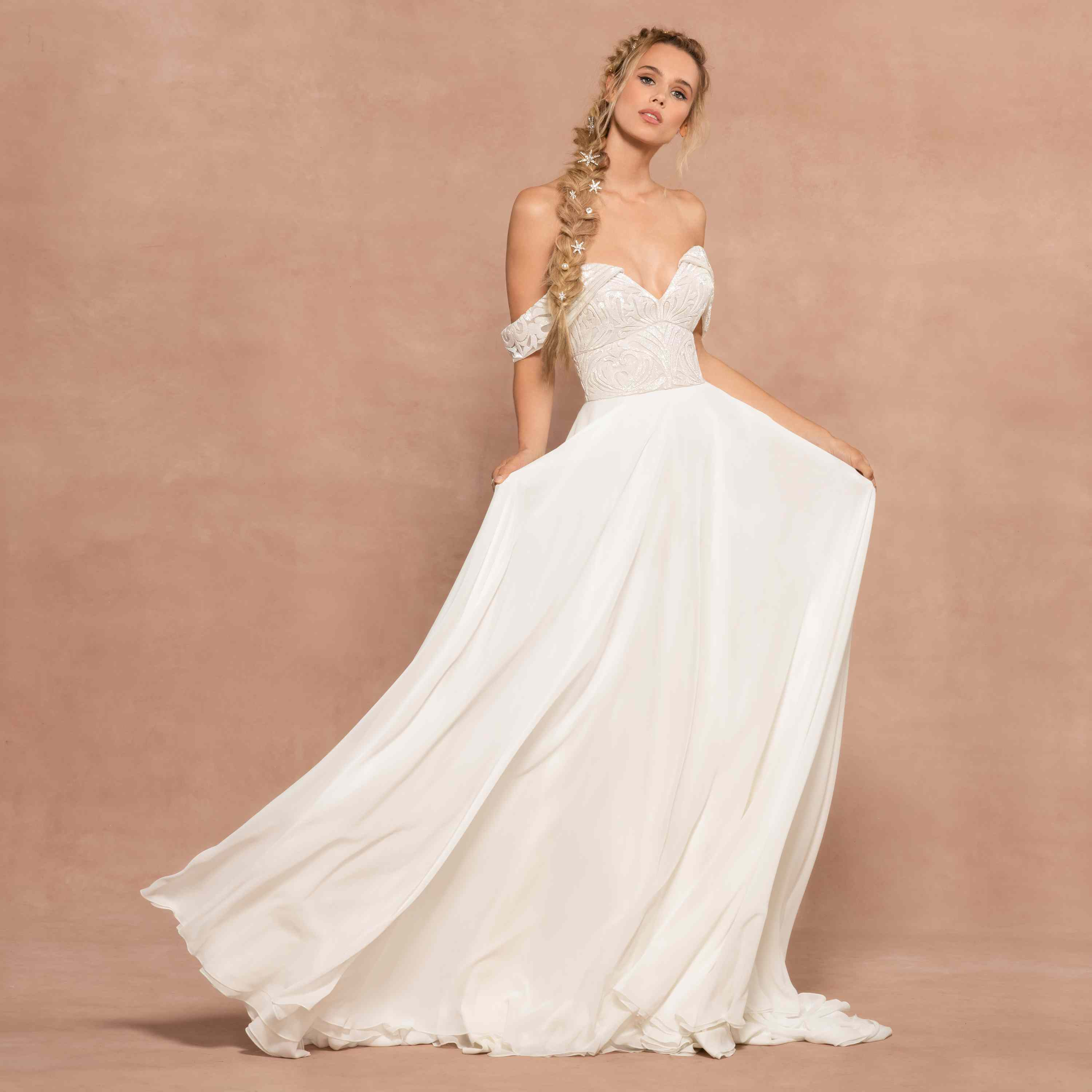 Model in ivory chiffon A-line gown with beaded bodice and off-the-shoulder sleeves