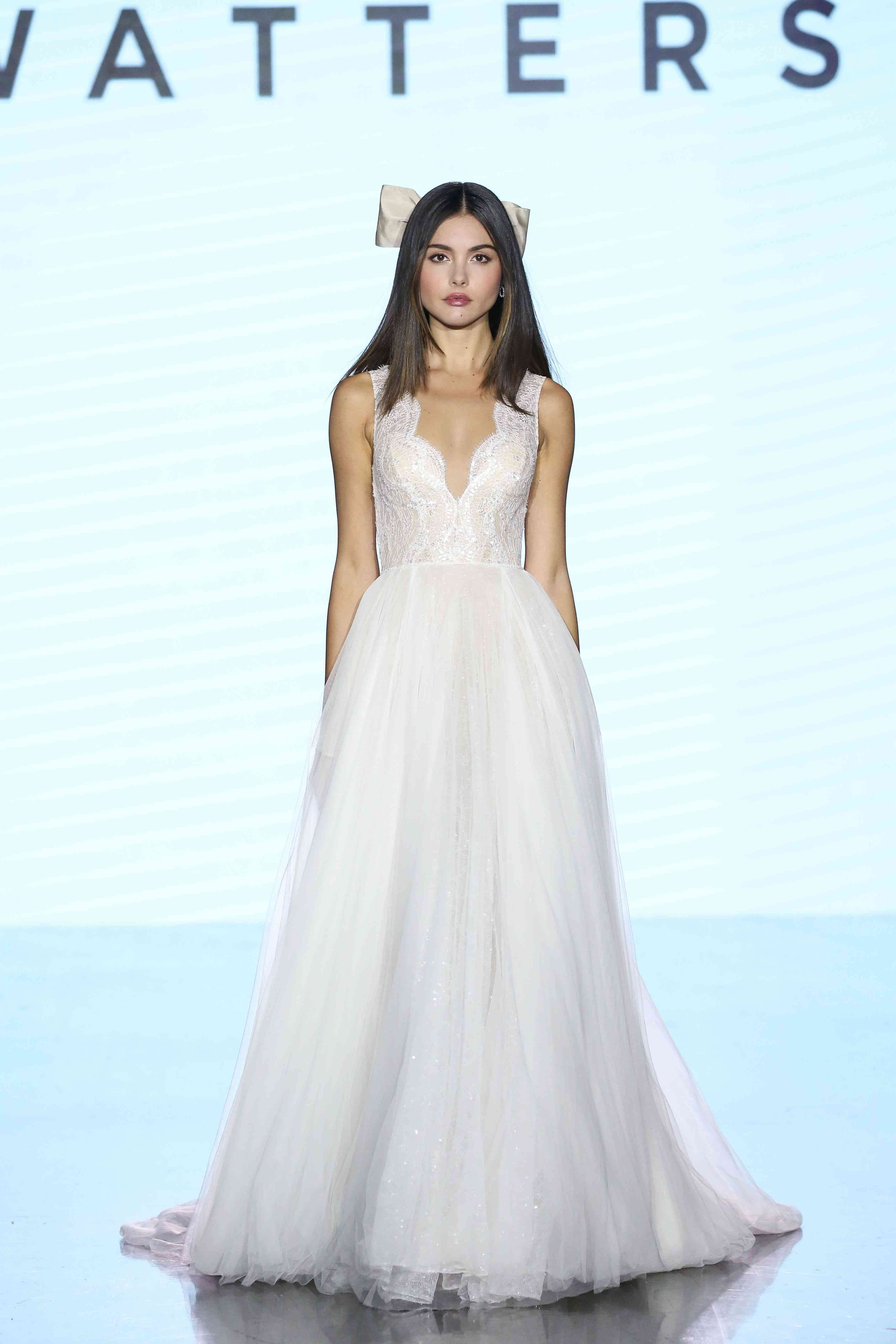 Model on runway in bridal ballgown with a scalloped plunging neckline, lace bodice, and tulle skirt