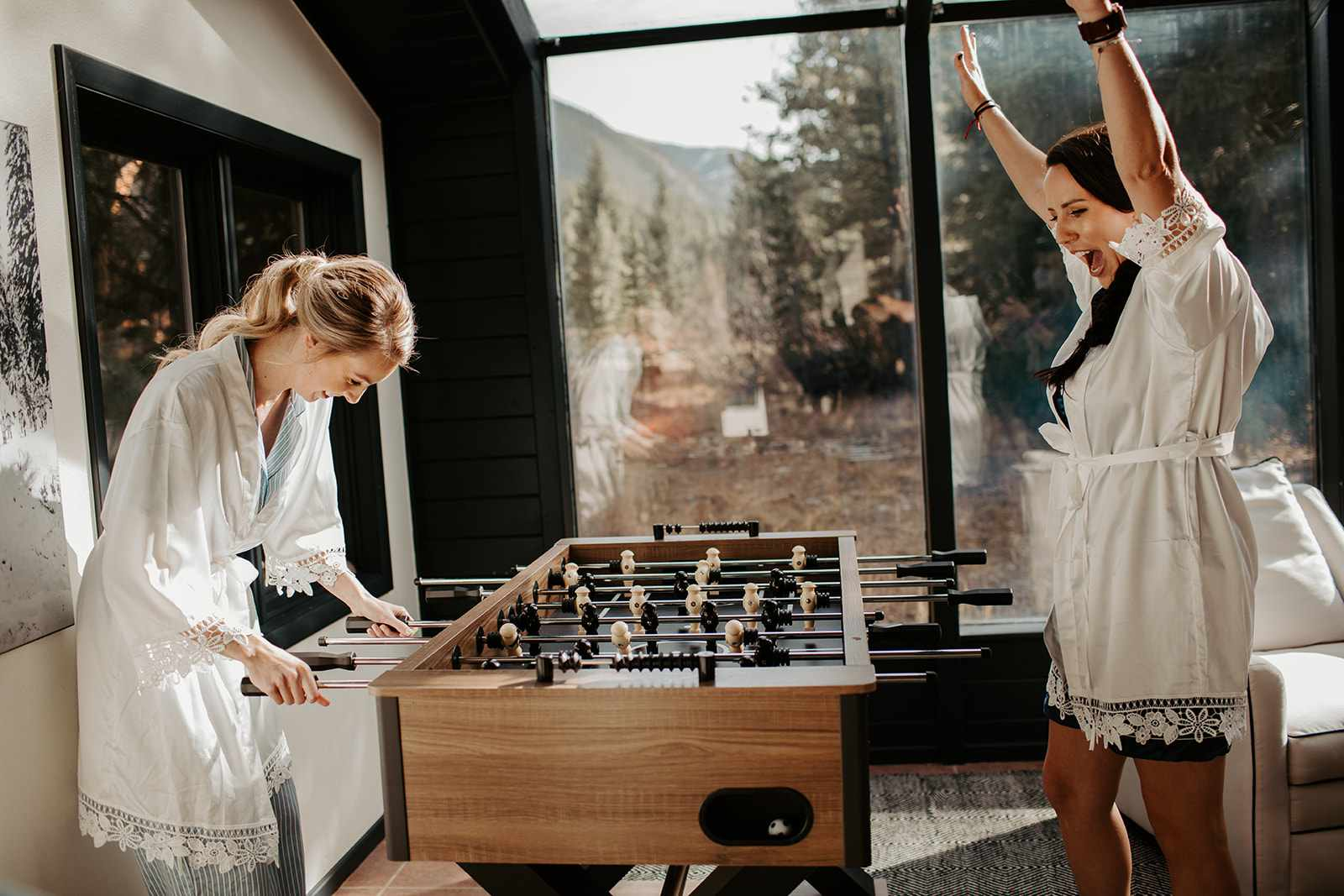 Brides playing foosball while getting ready