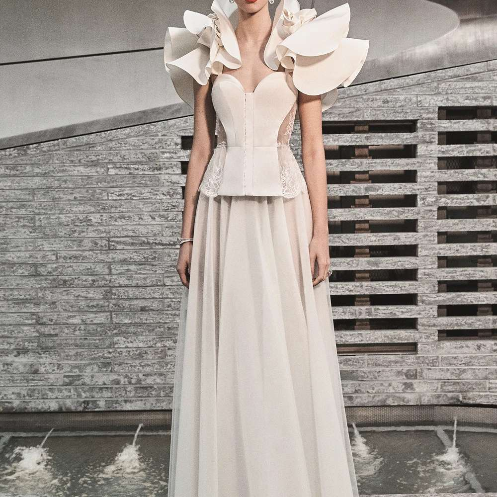 Model in wedding dress with oversized ruffle sleeves and tulle skirt