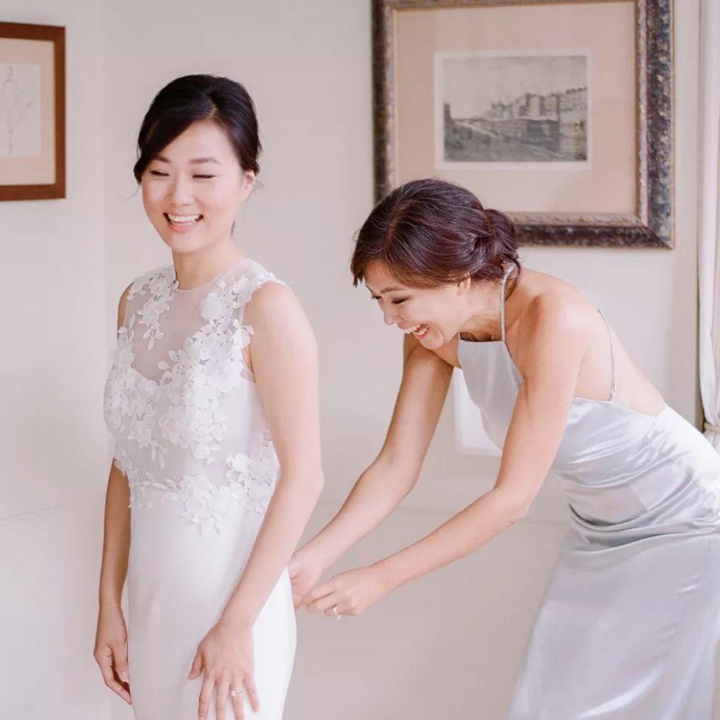 Bridesmaid zipping bride into dress