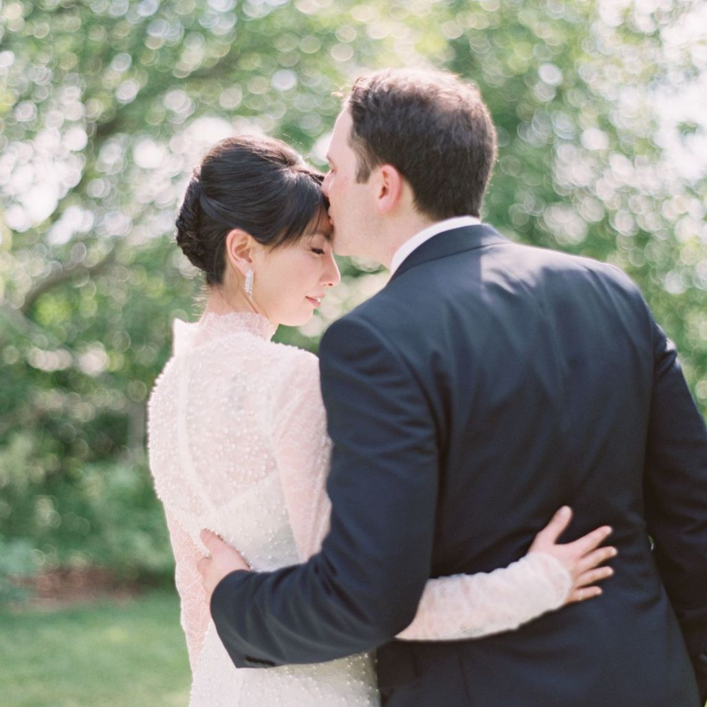 Groom kissing bride on the forehead