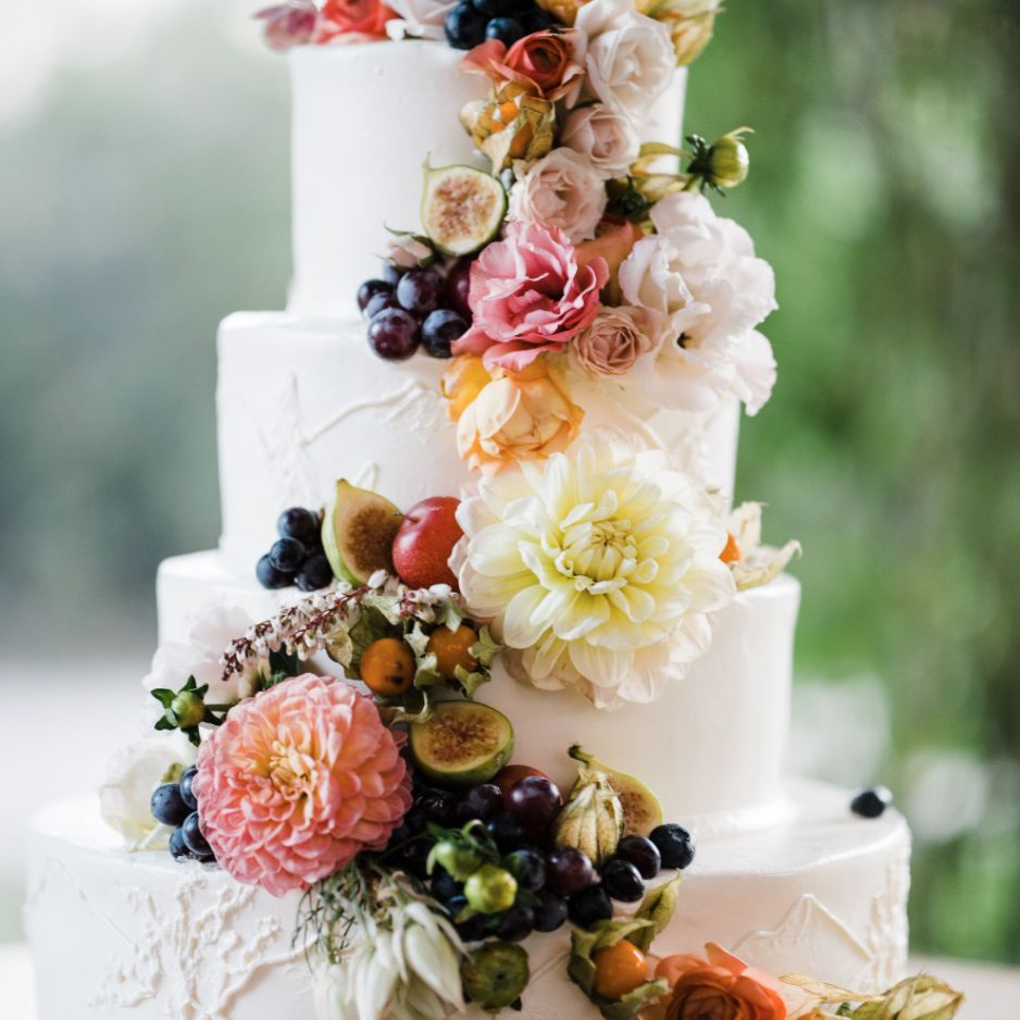 White tiered cake with fresh fruits and flowers cascading down