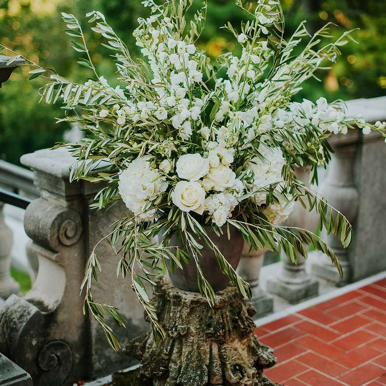 An all-white floral arrangement of hydrangeas and delphiniums