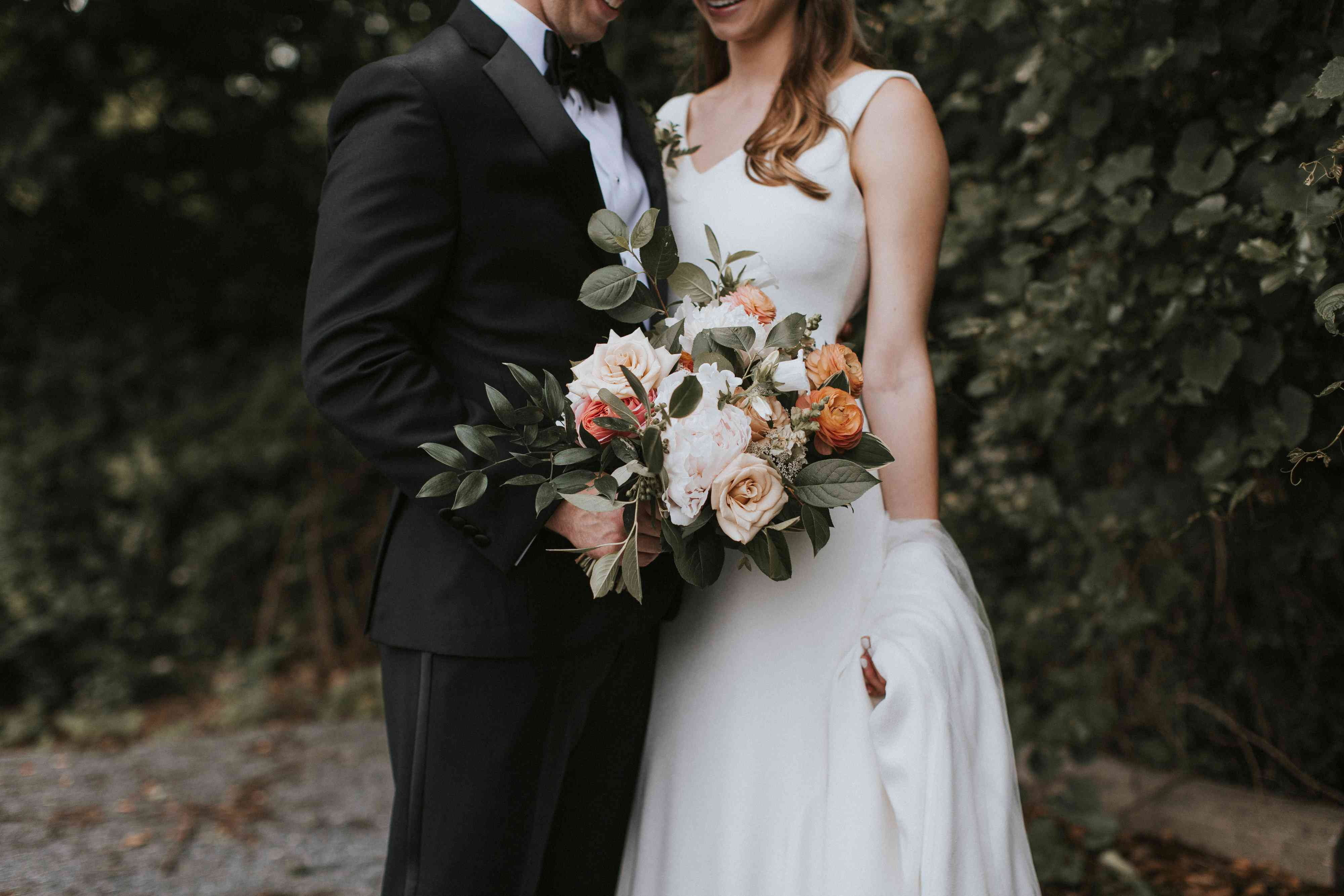 Bride and groom standing side by side holding bouquet