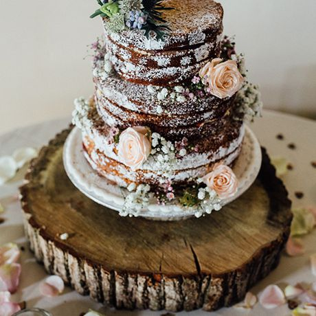 A naked chocolate wedding cake, dusted with powdered sugar and sitting atop a rustic wooden tree stump