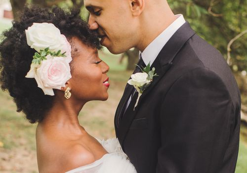 Bride with flowers in her hair being kissed by groom