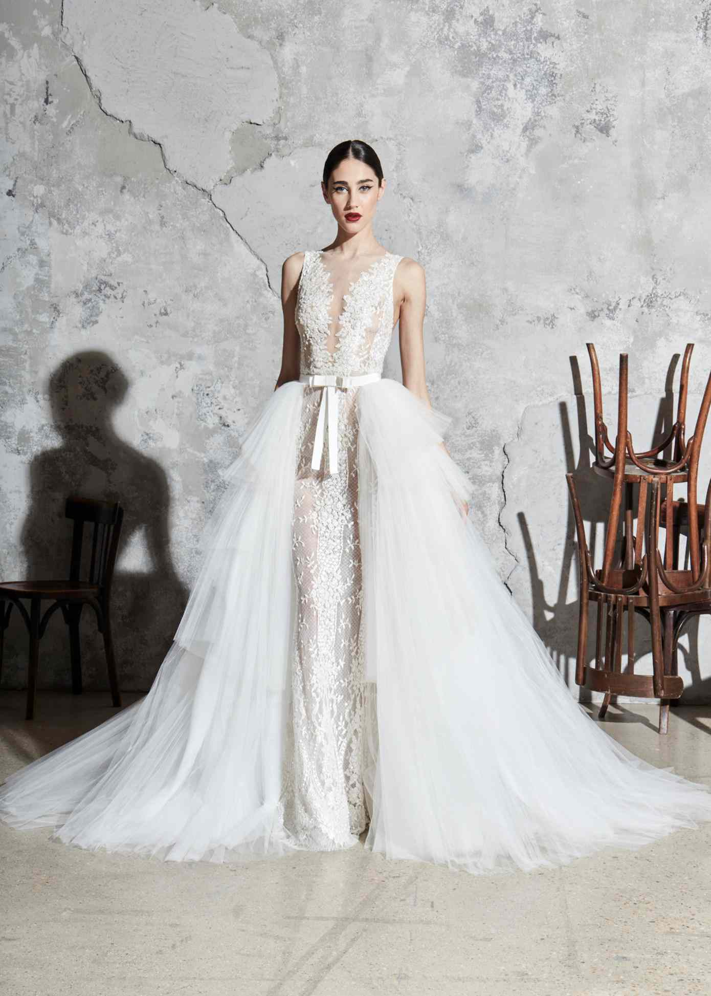 Model in a floral-embroidered sheath gown with an illusion neckline, a white bow belt, and a tiered tulle overskirt
