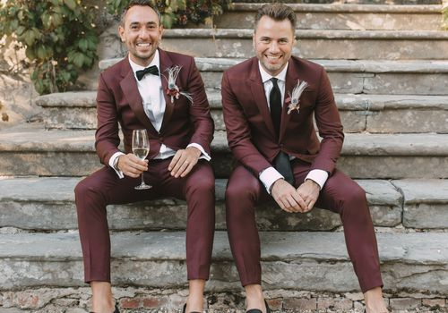 Groom and best man sitting on steps and smiling