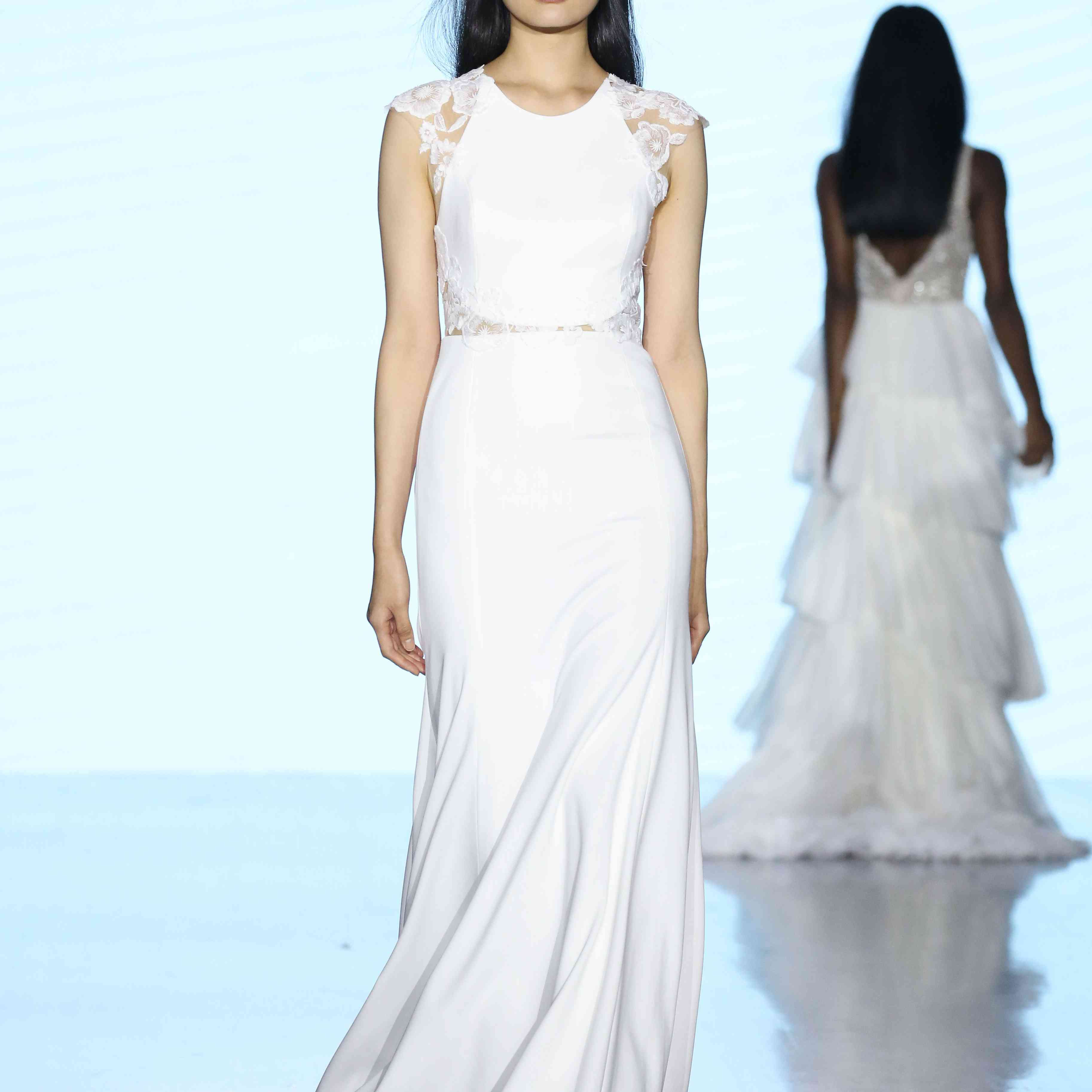 Model in crepe sheath dress with floral lace cap sleeves and side cutouts