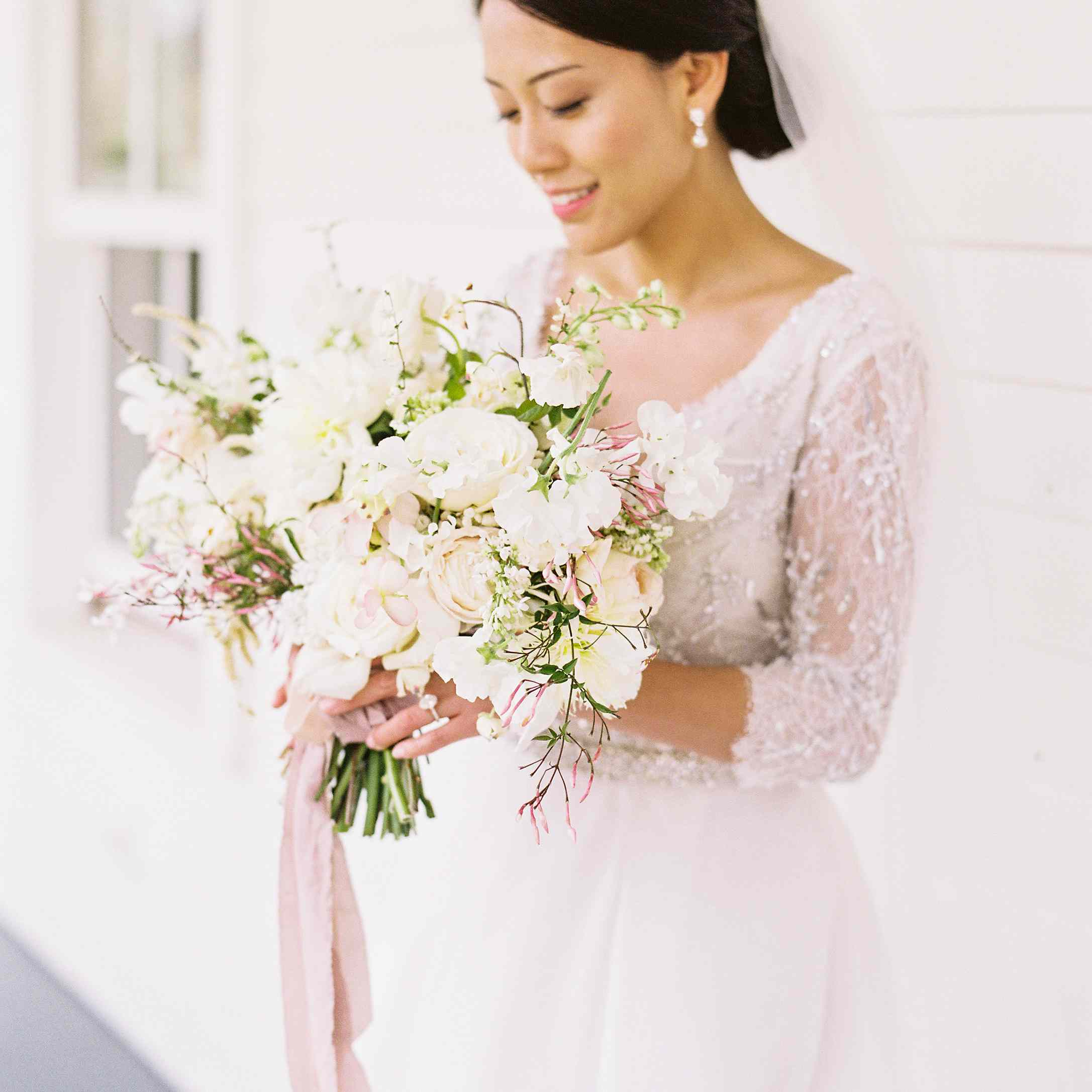 Bride holding an all white bouquet of dogwood and roses