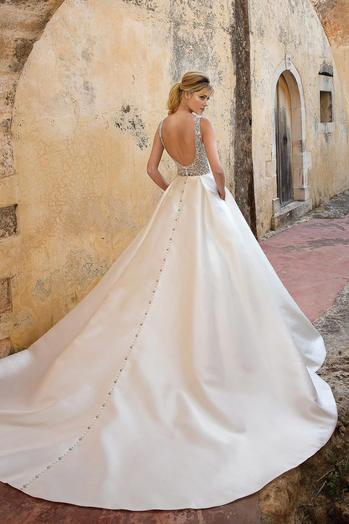 Model in crystal embellished ball gown with long train and buttons