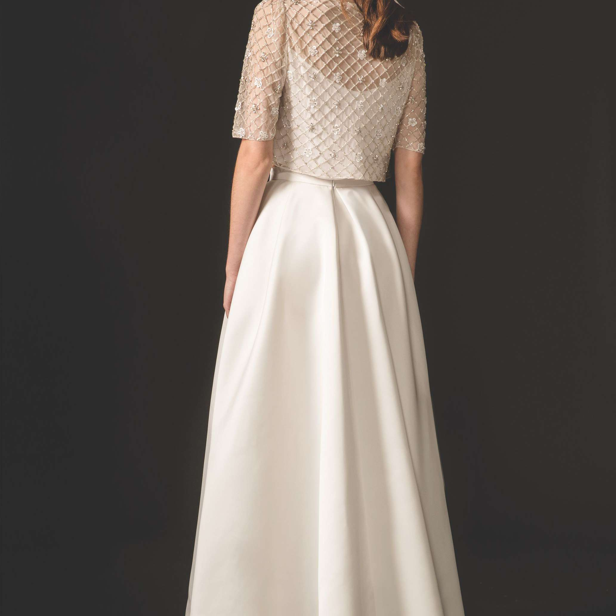 Model in satin gown with beaded short-sleeved top
