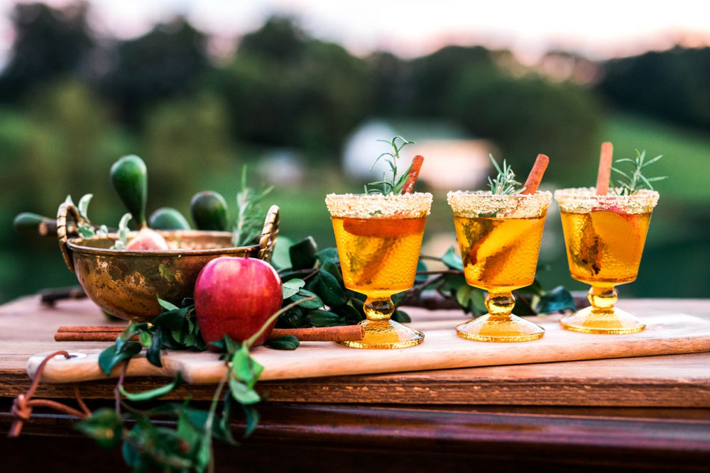 Apple cider cocktails in sugar-rimmed glasses on an autumnal display