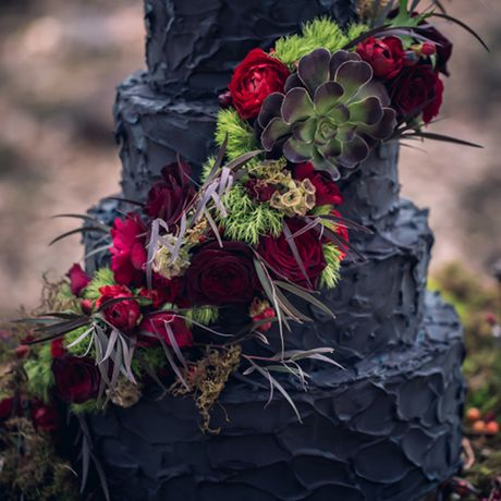 A four-tiered black wedding cake by Artistic Bites adorned with fall foliage