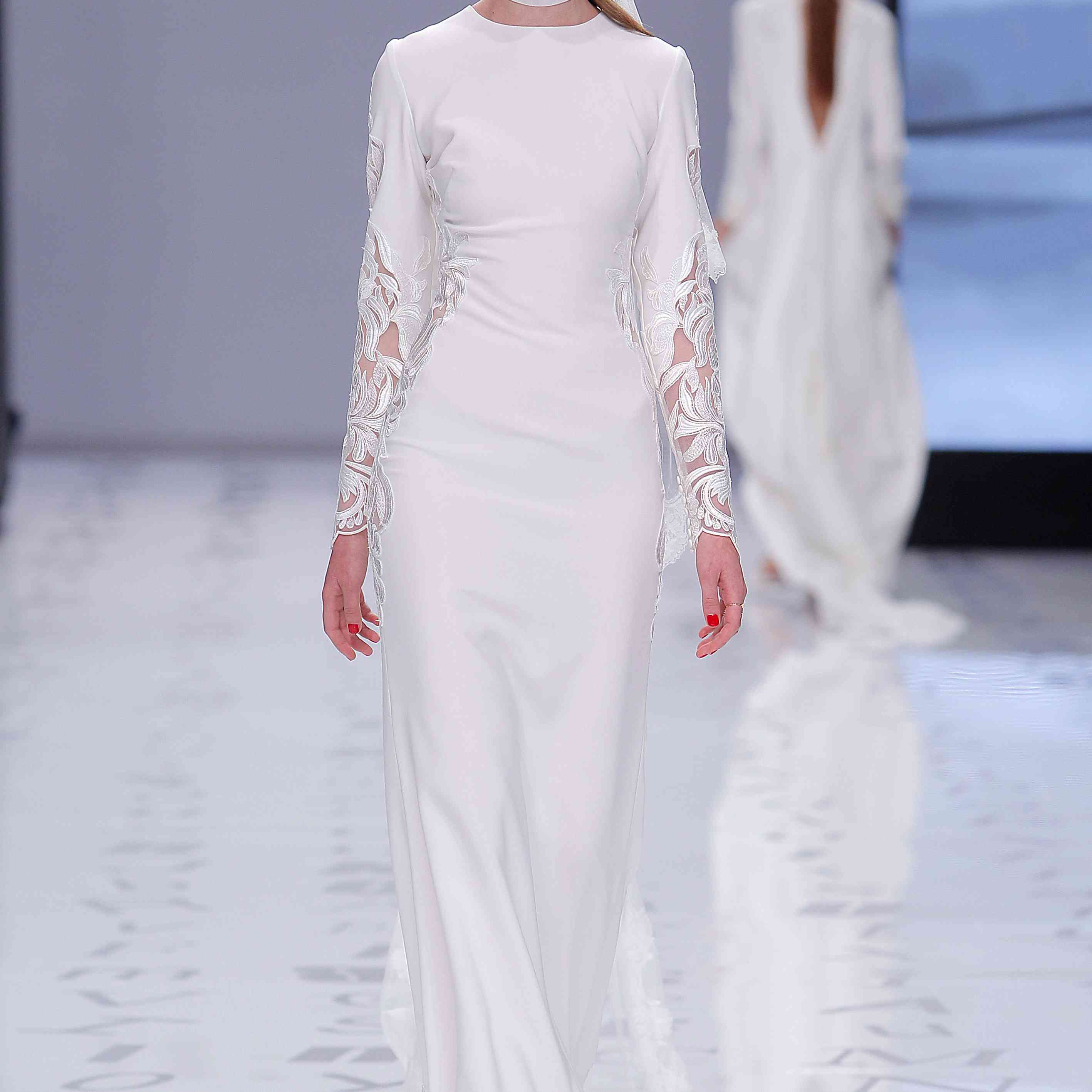 Model in a long-sleeve fitted sheath dress with embroidery along the sleeves and sides.