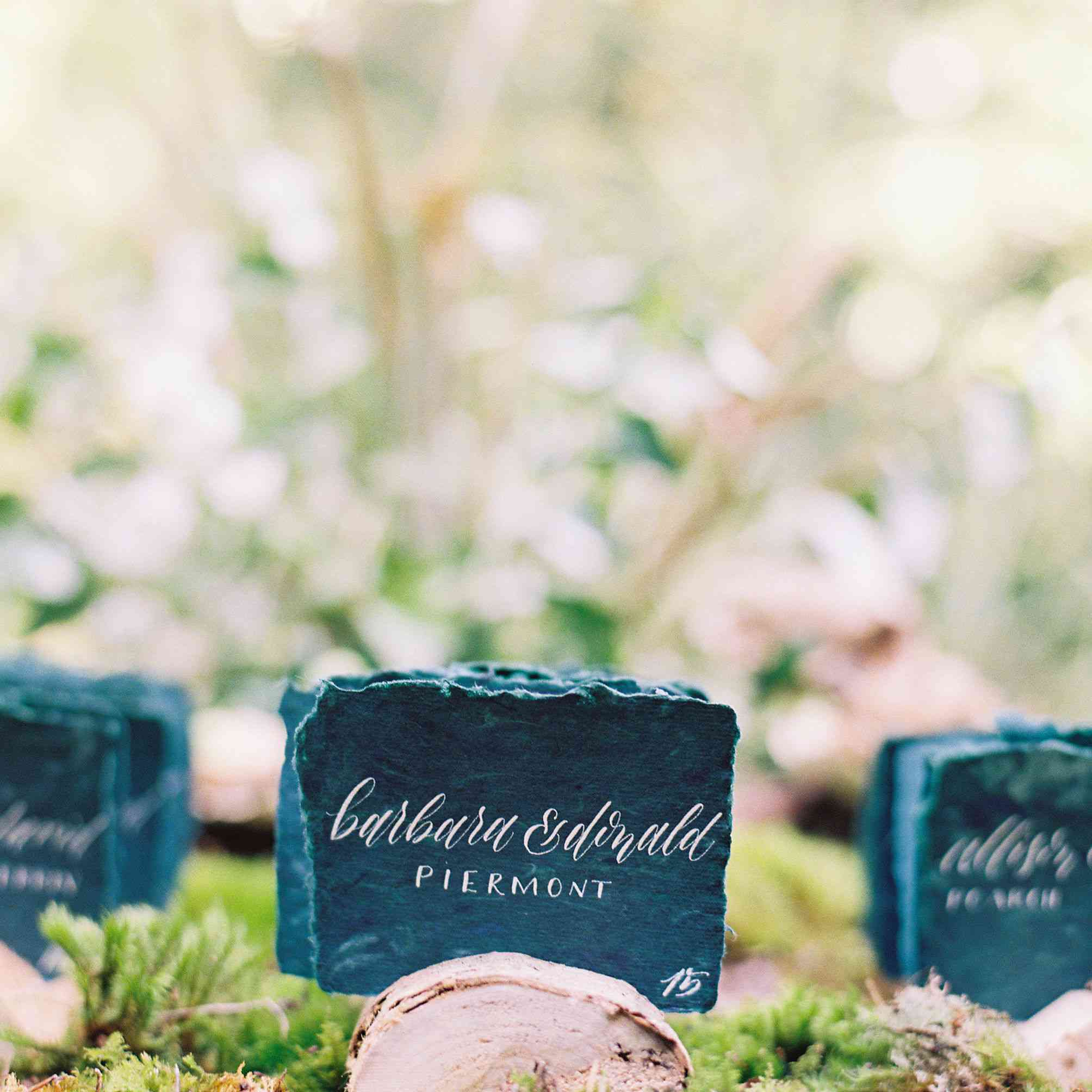 Handmade paper escort cards placed in moss