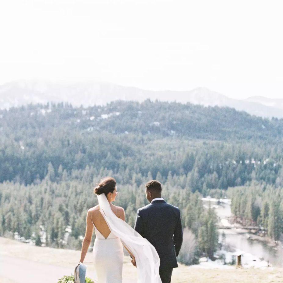 Newlyweds walking towards slopes of Cascade Mountains