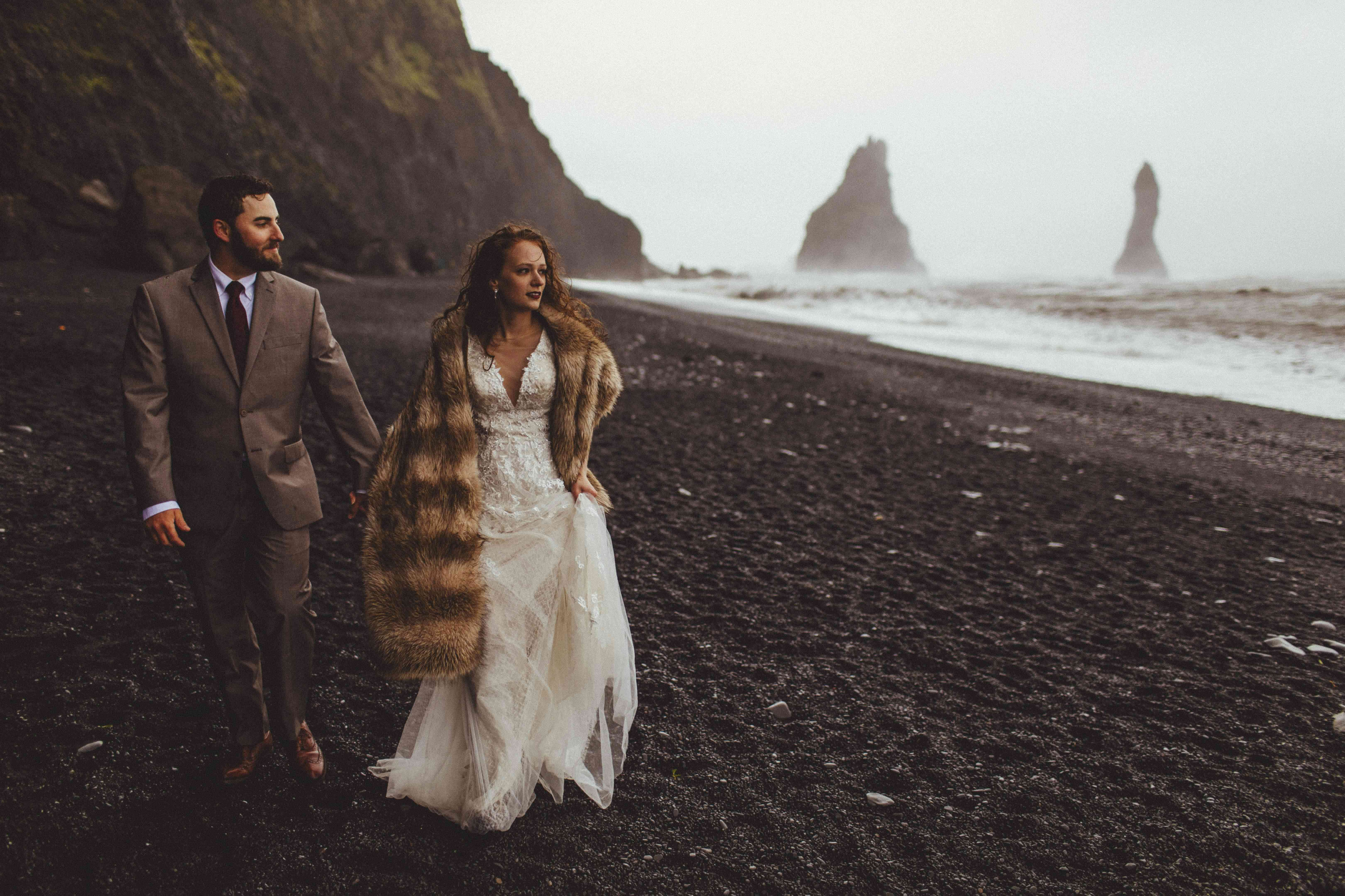 Couple holding hands on a black sand beach in Iceland