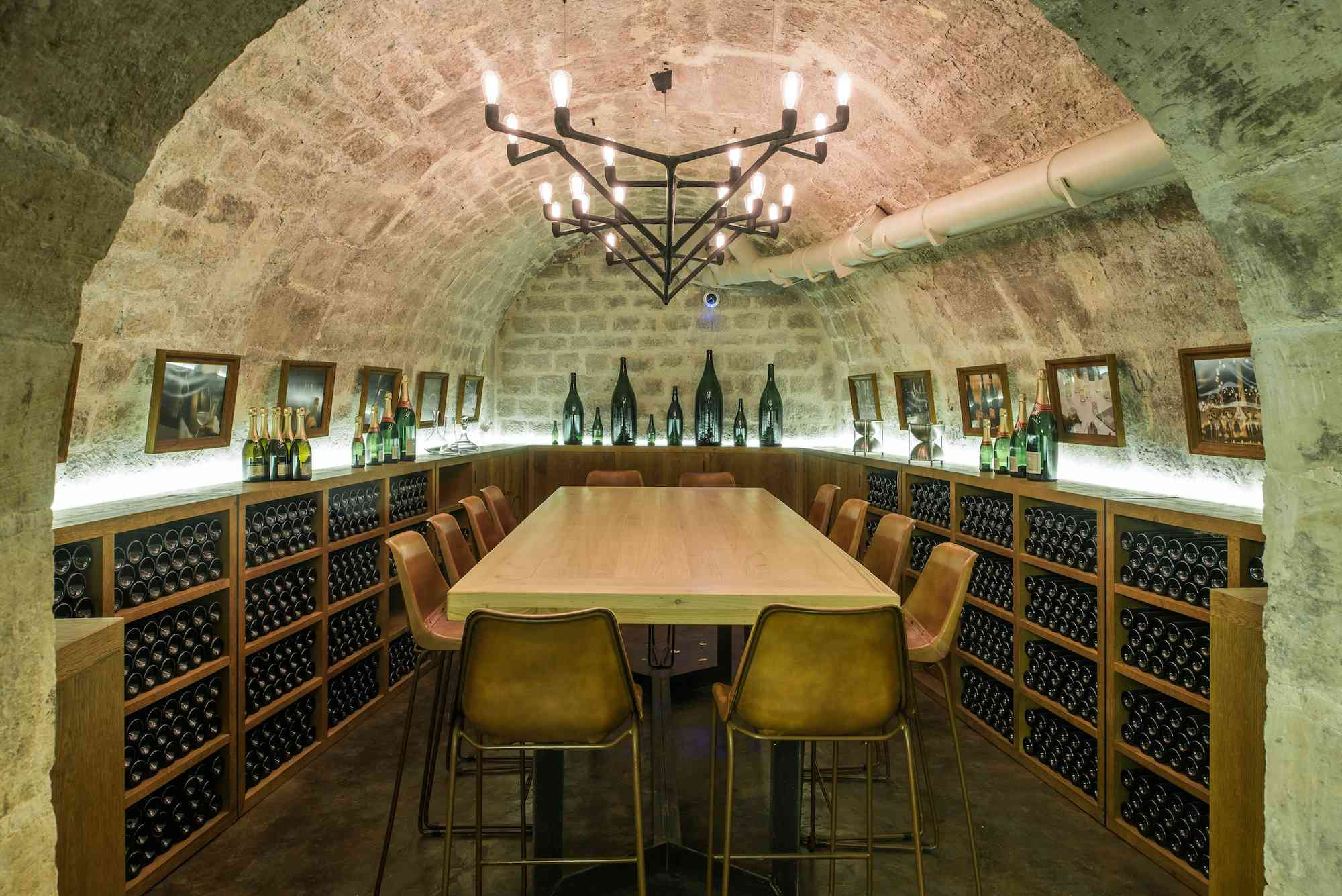 Underground wine tasting room with wine bottles surrounding the center table