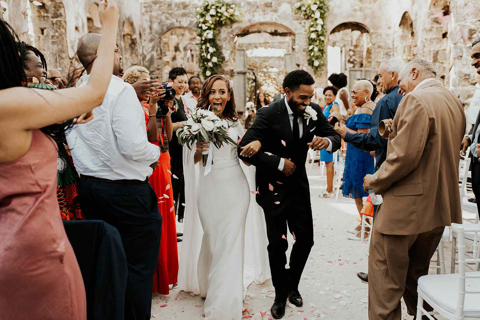 Bride and groom walking back up the aisle after ceremony