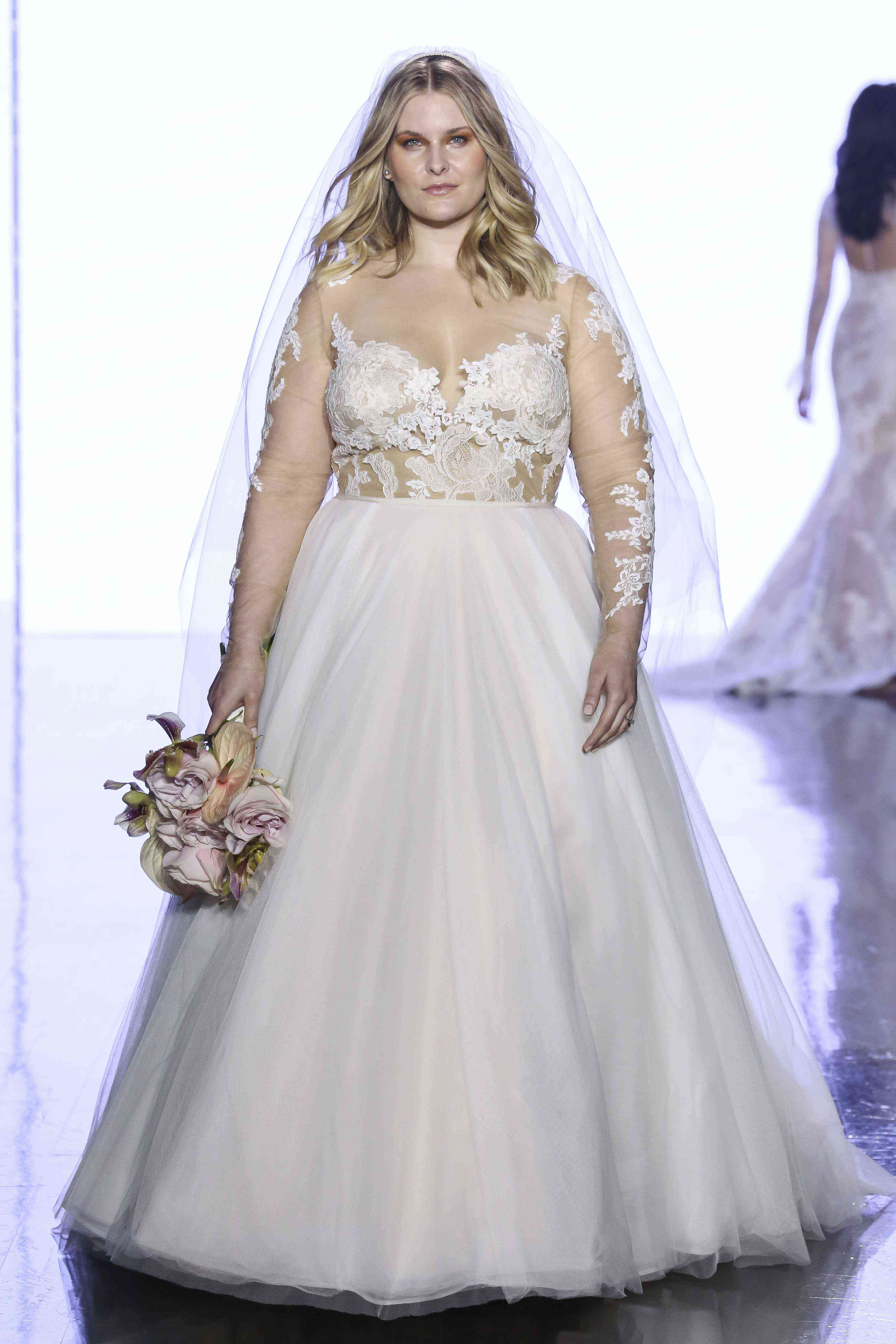 Model in ballgown with lace-embroidered illusion long sleeves and bodice and an illusion neckline