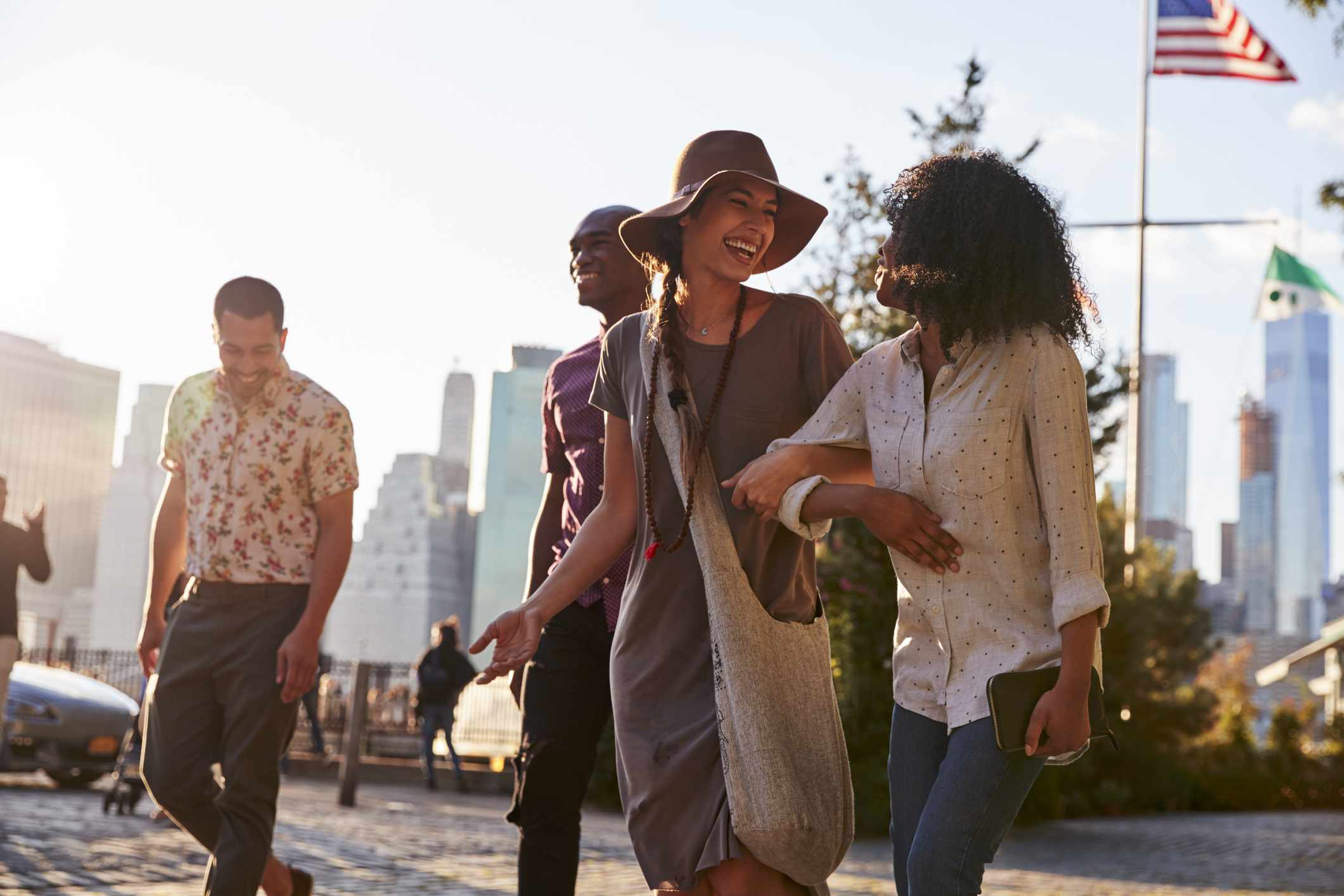 Four friends walking outside with Manhattan skyline in the background