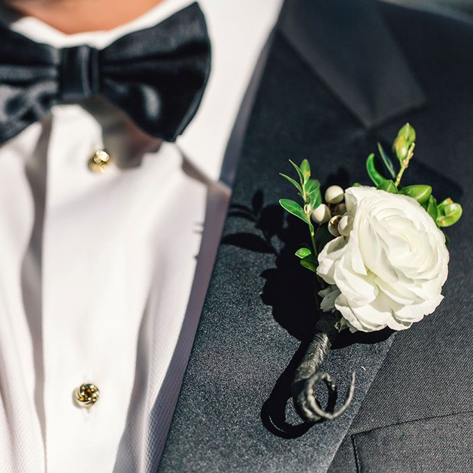 A white ranunculus boutonniere, accented with greenery and snowberries, created by Oak Leaf Florist