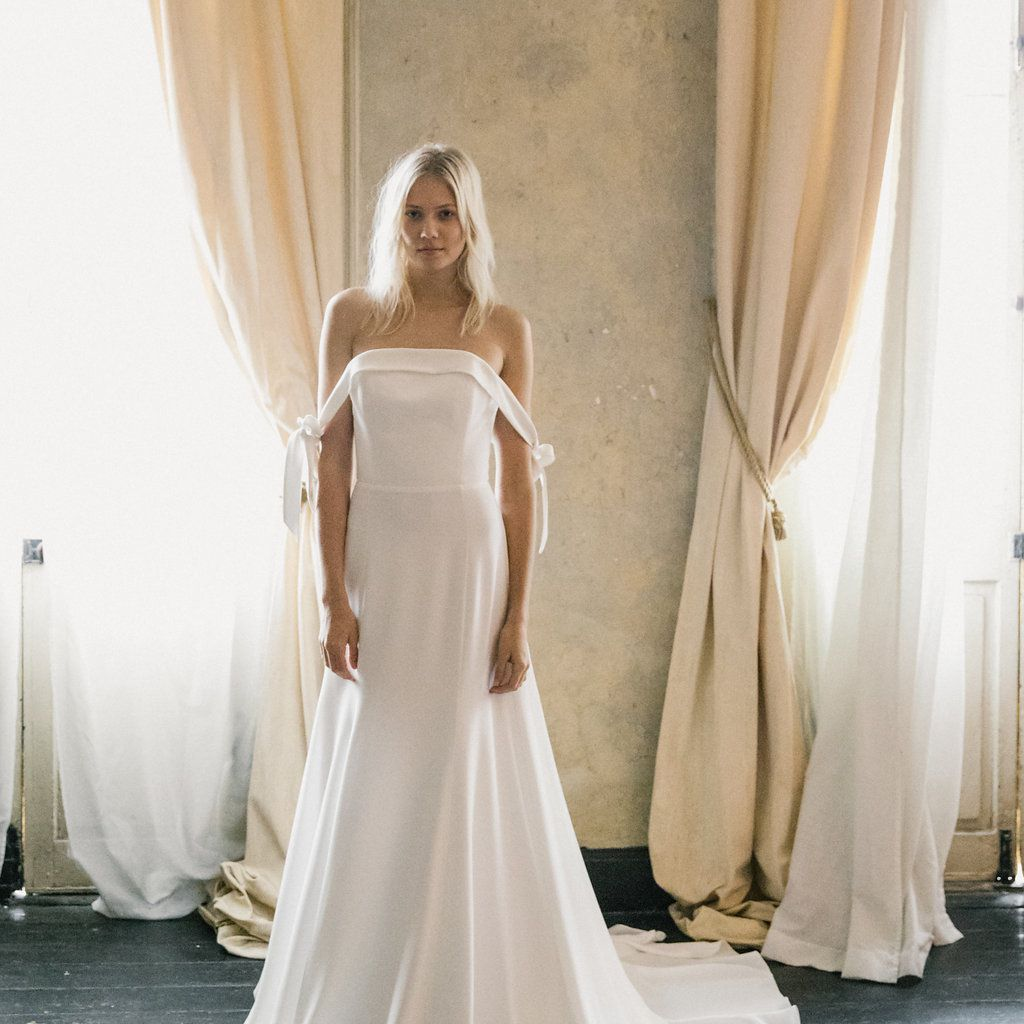 Model in white gown with tied off-the-shoulder sleeves