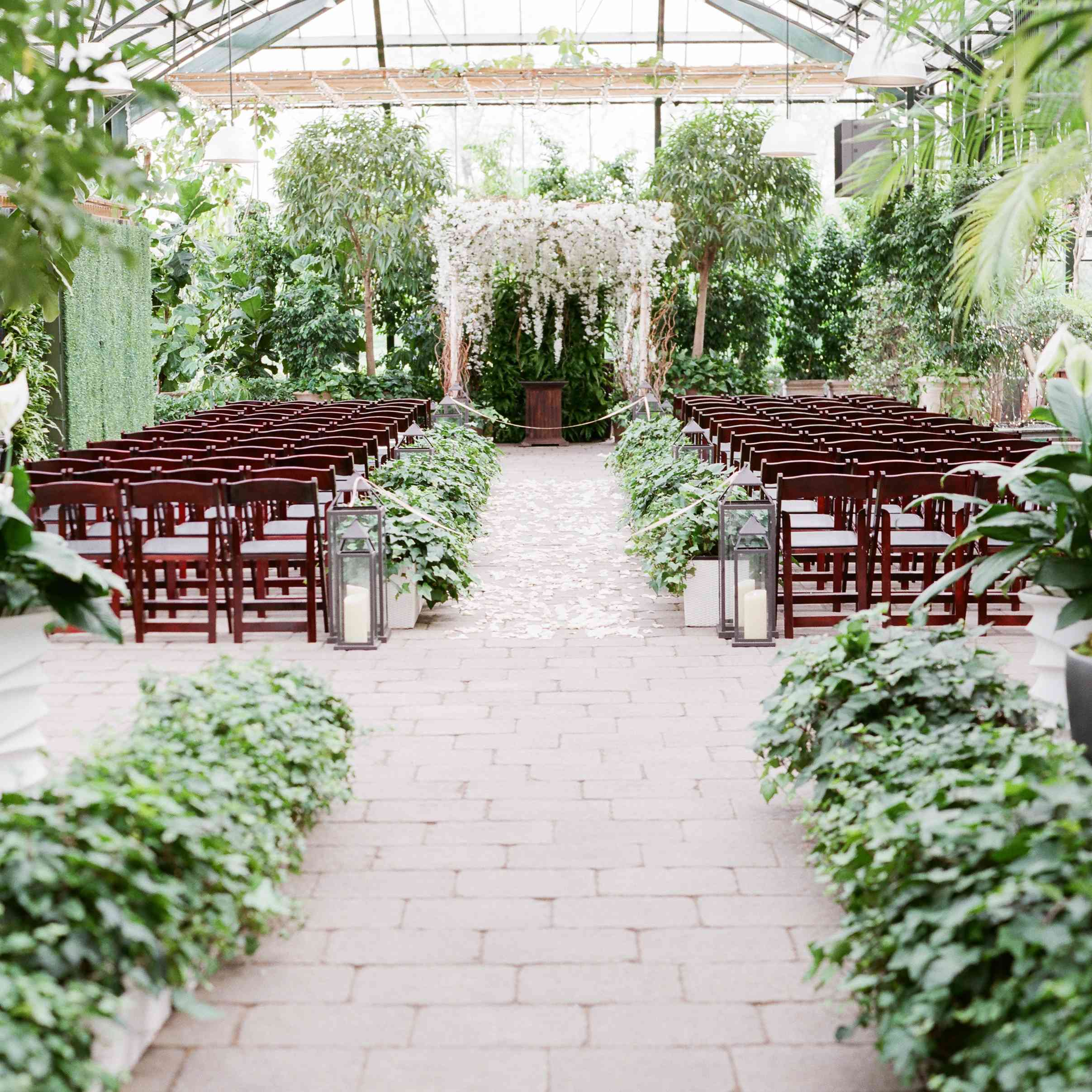 Greenhouse wedding with brick flooring and aisle lined with greenery