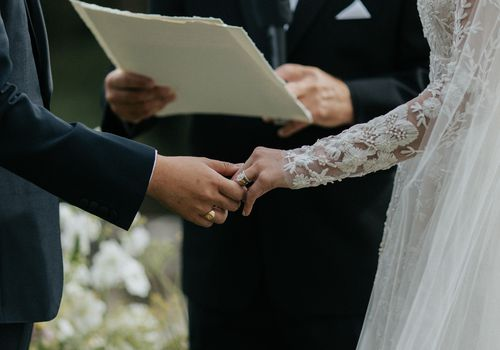 bride and groom wedding rings holding hands