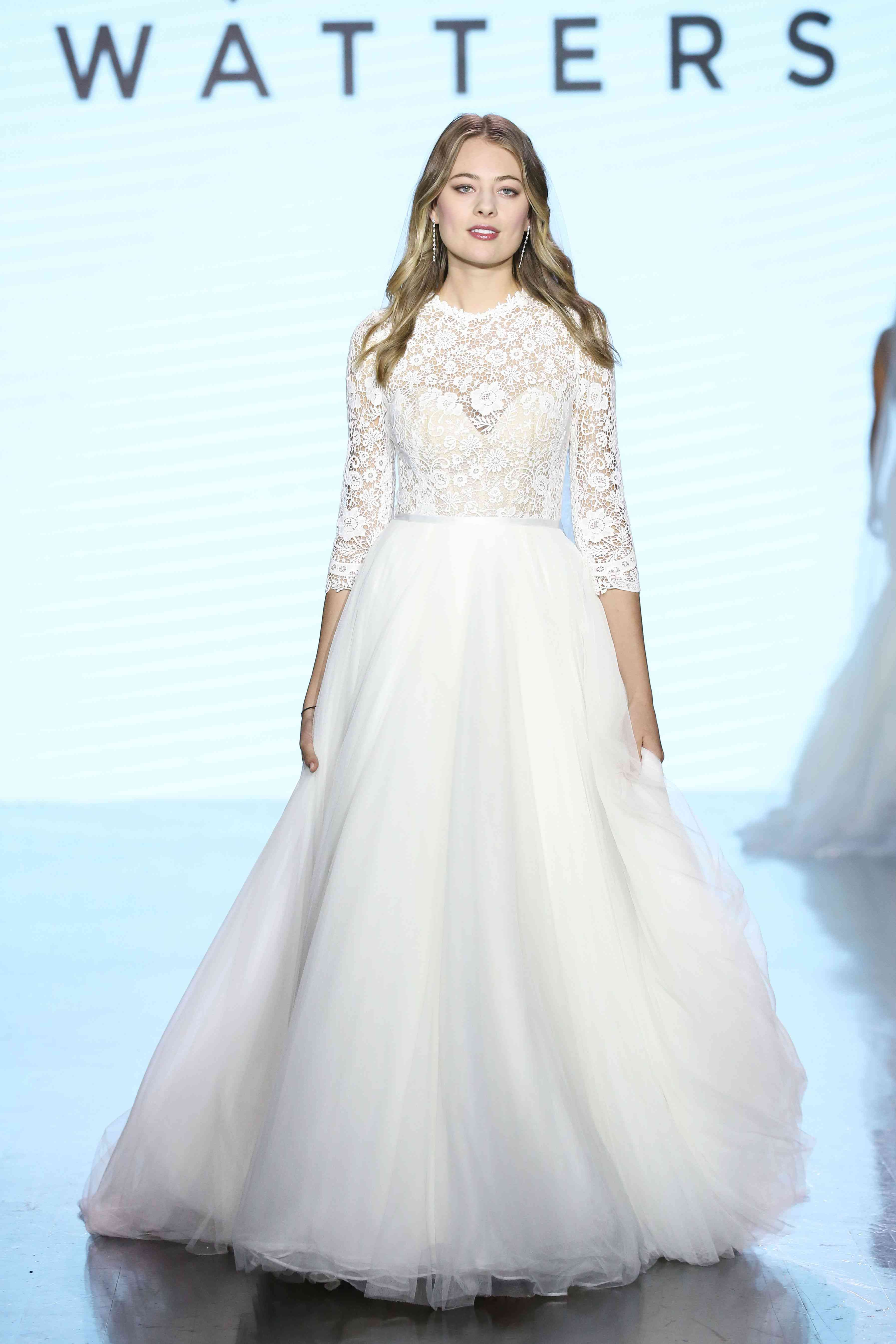 Model on runway in three-quarter-sleeve ballgown with a floral lace high-neck bodice and a tulle skirt