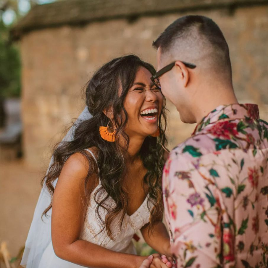 Newlyweds laughing and holding hands