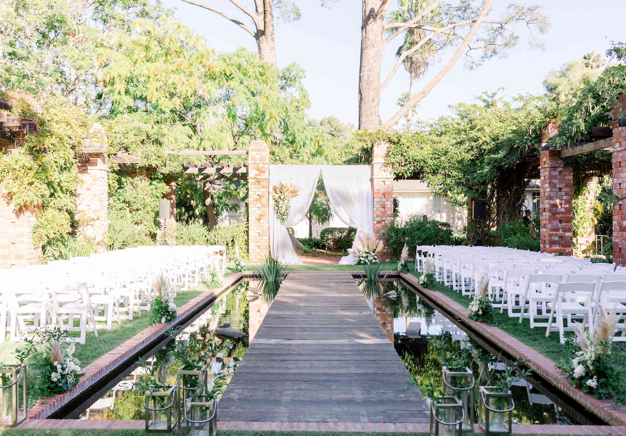 Ceremony with a boardwalk aisle crossing a garden pond