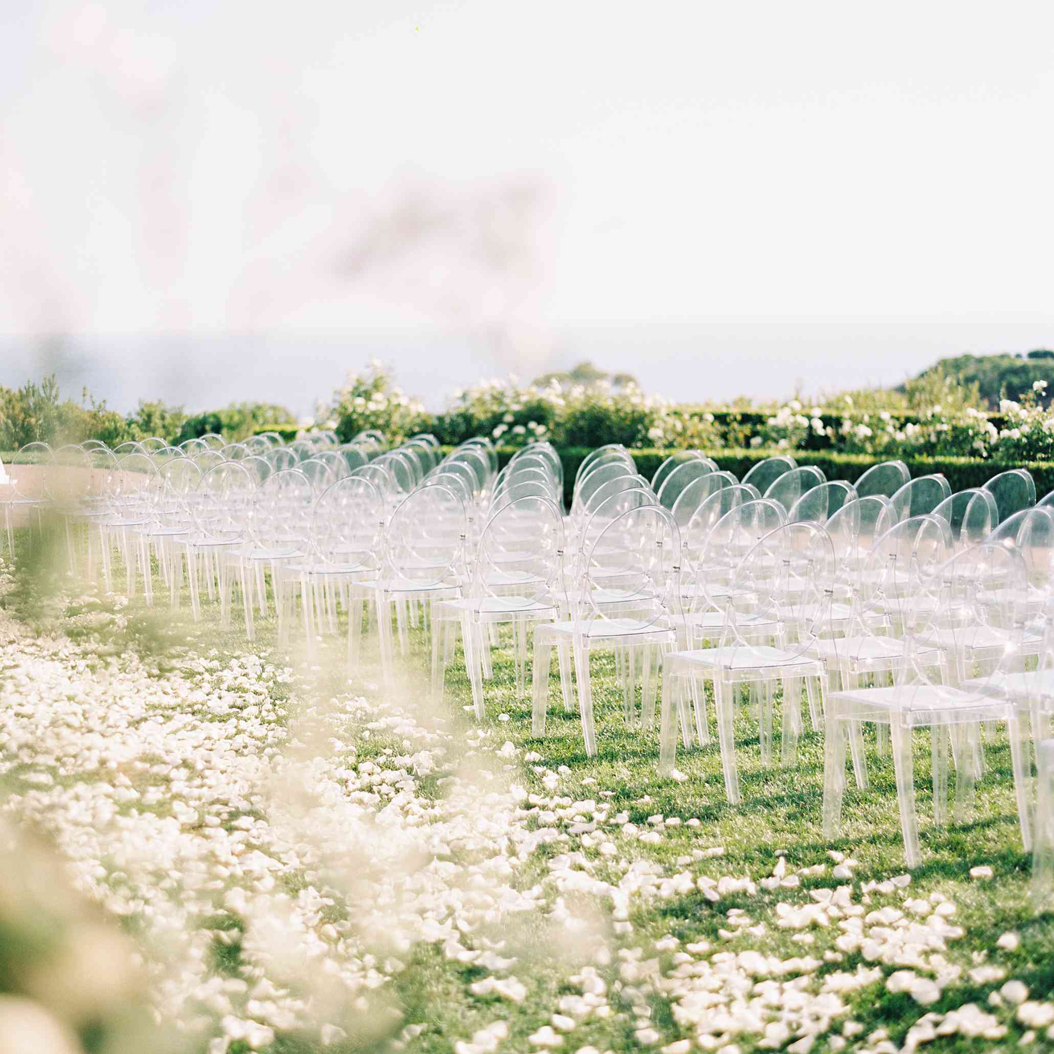 White flower petals lining the wedding aisle with acrylic chairs on grass