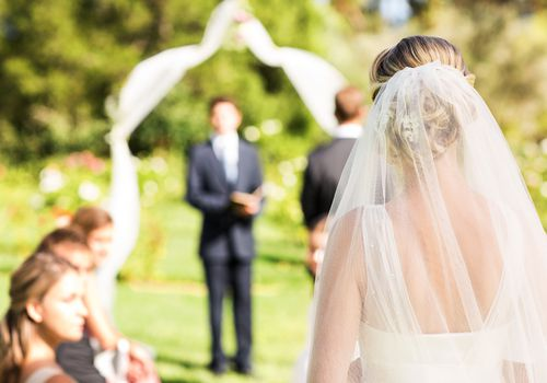 Back of bride with veil walking down aisle