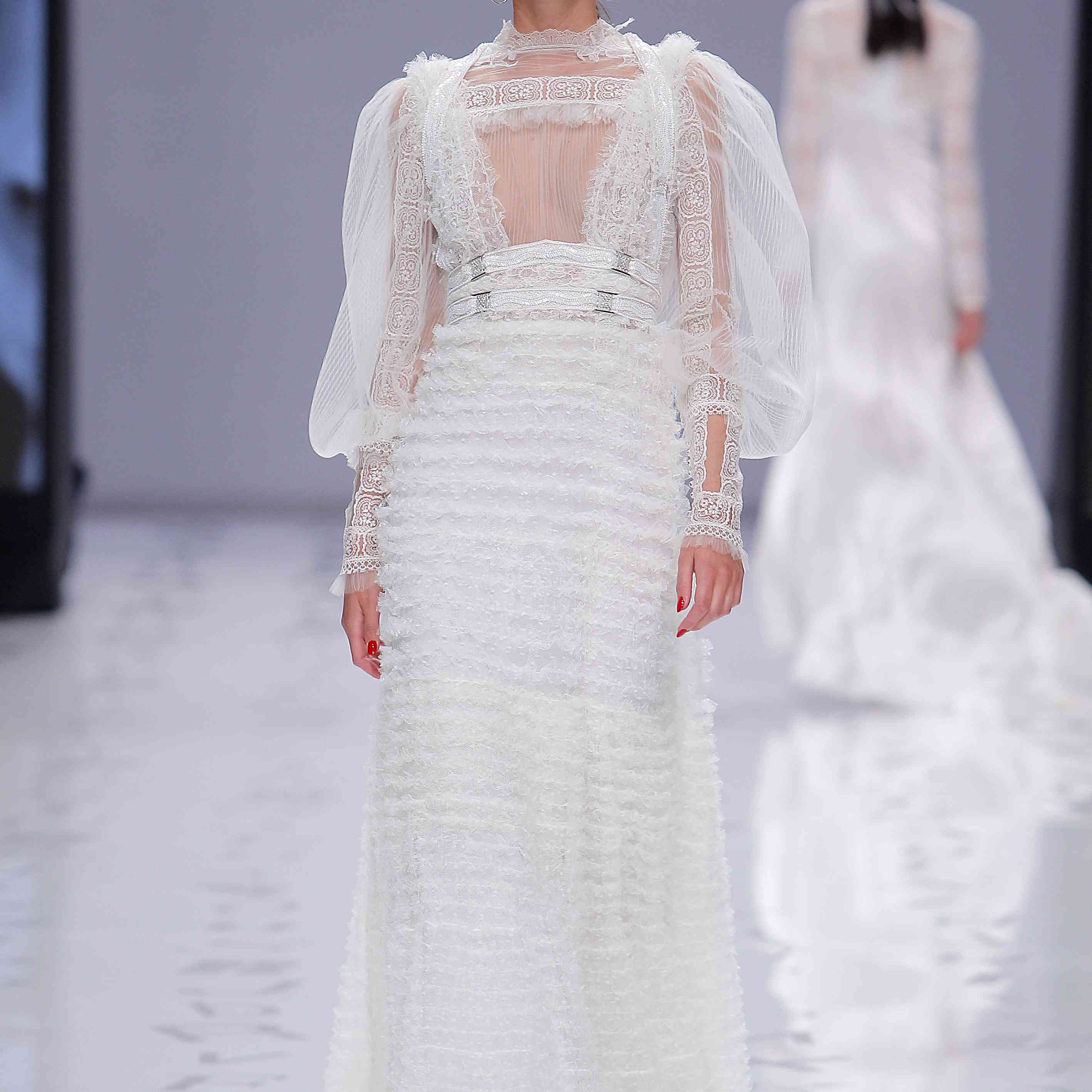 Model in high-neck lace and tulle sheath dress with long puff sleeves, a ruffled skirt, and a beaded double waistband