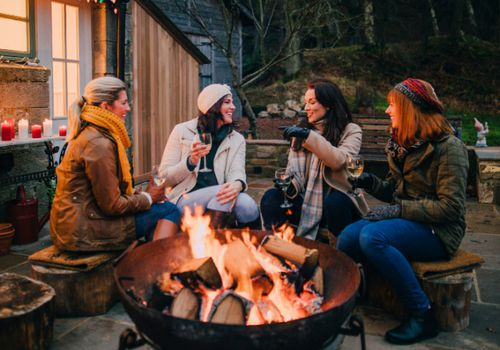 Four women drinking wine around a firepit