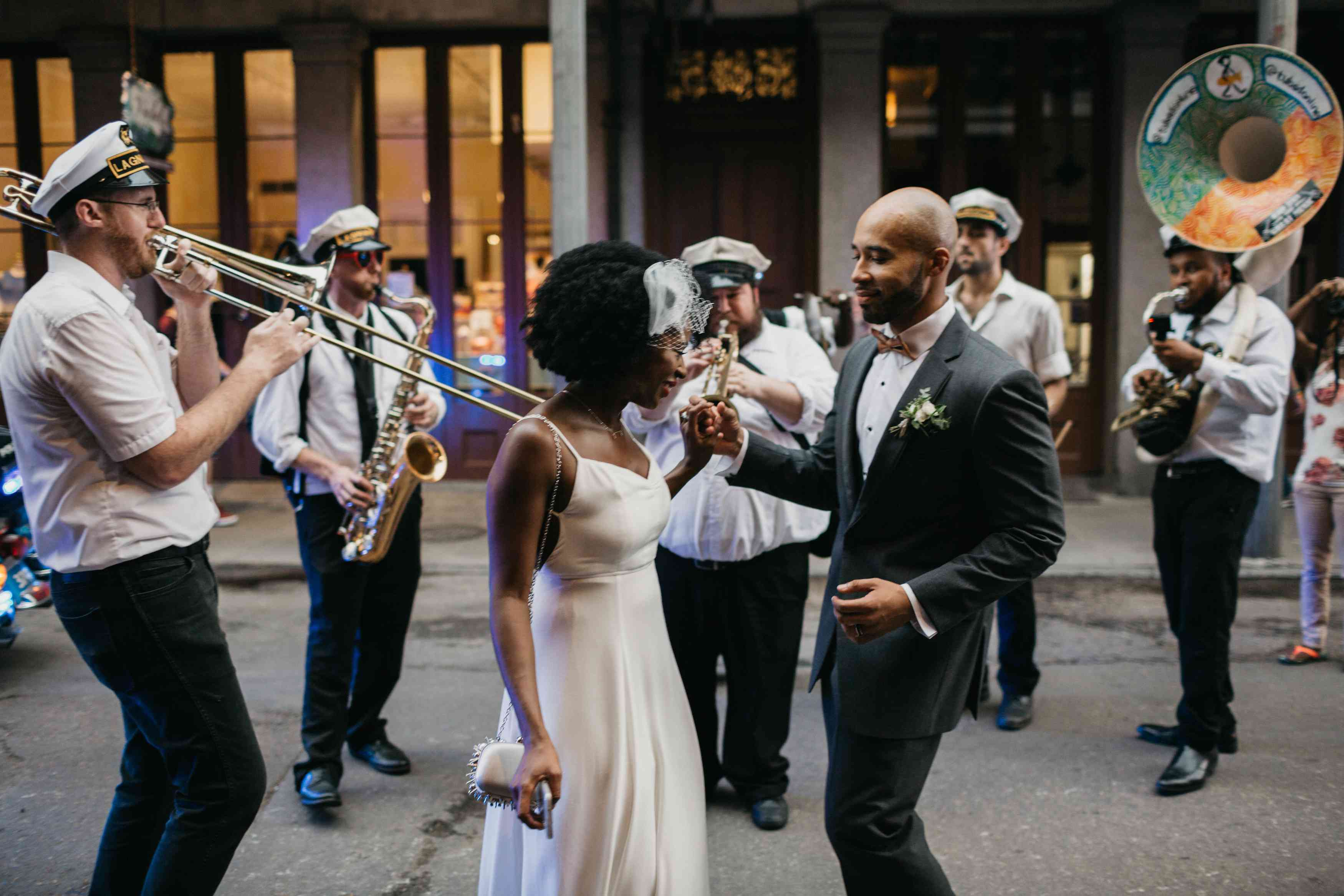 A married couple dancing in a second line parade in New Orleans