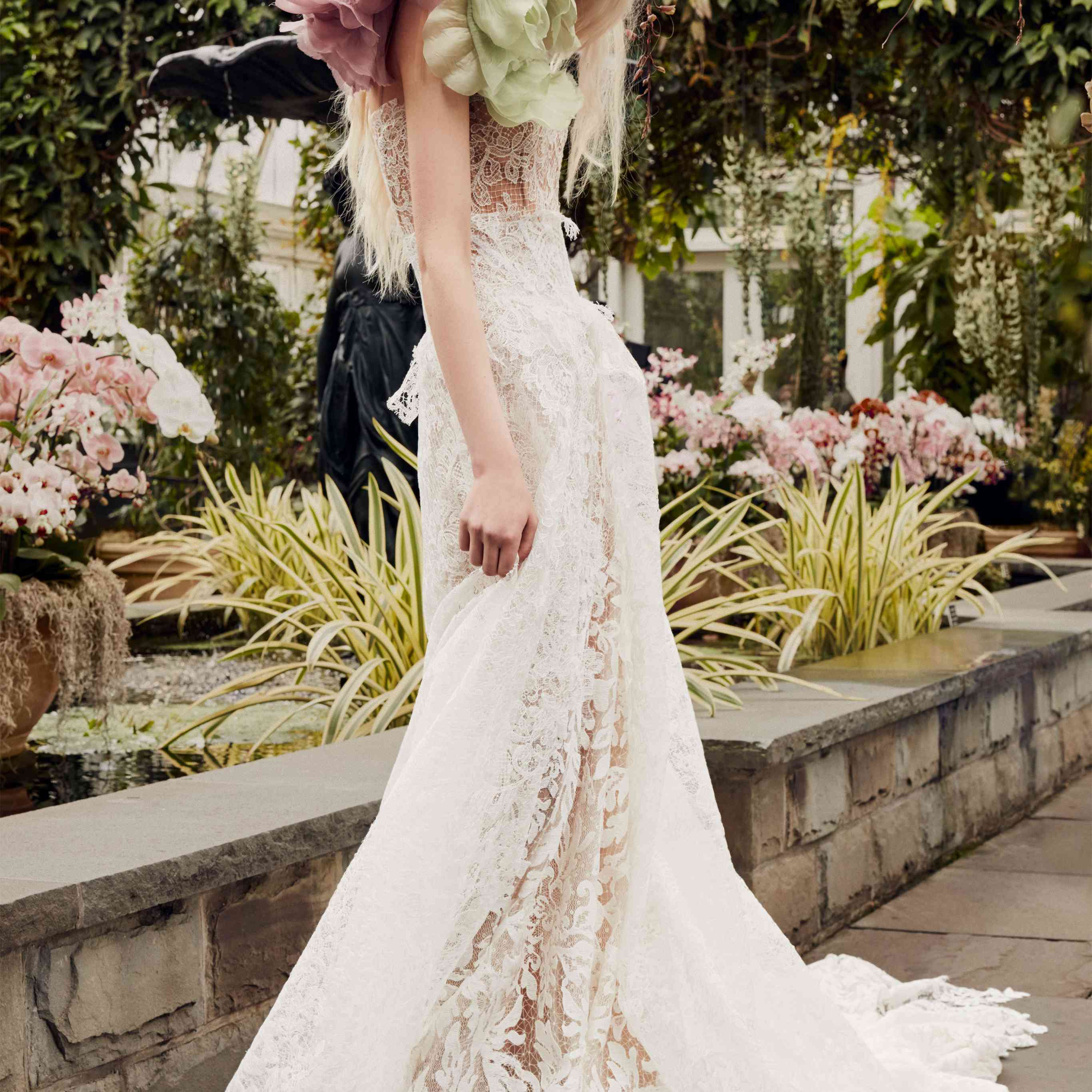Model in allover lace gown with pink and green flower accents at the shoulder