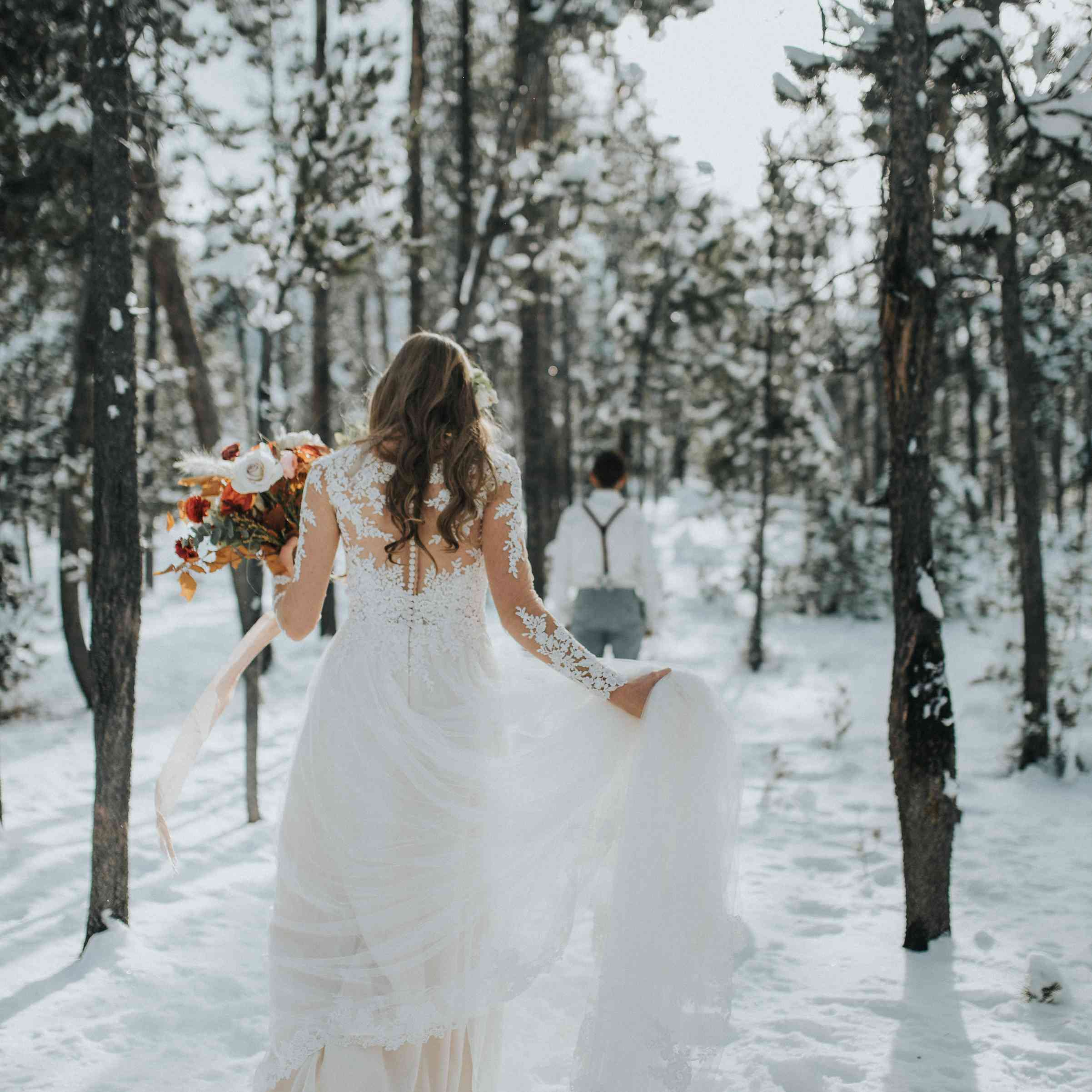 Bride walking through the woods in the snow holding a bouquet