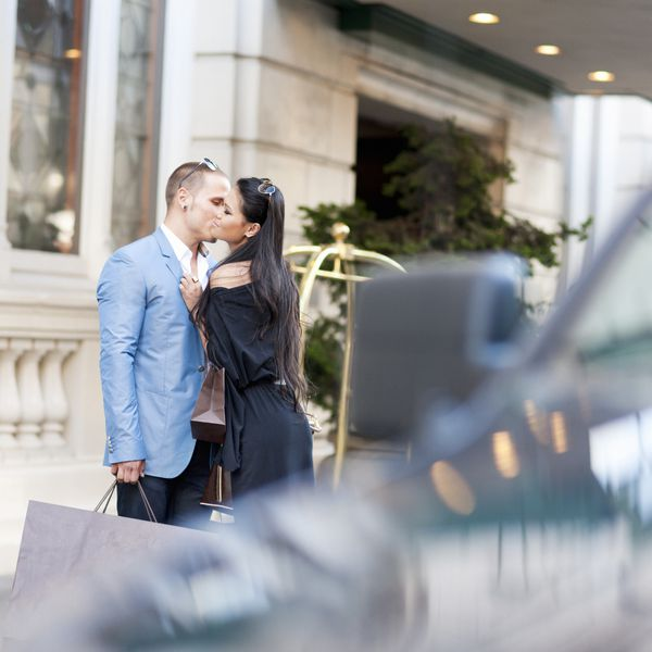 man and woman kissing outside a building