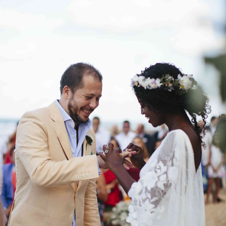 Bride putting gold ring on groom's finger
