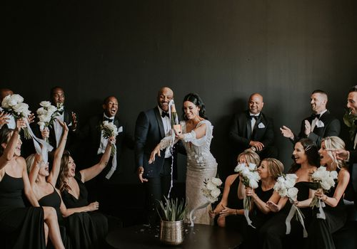 Bride and groom popping a bottle of champagne surrounded by bridal party